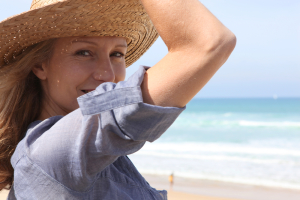 Woman holding onto her straw hat in a breeze