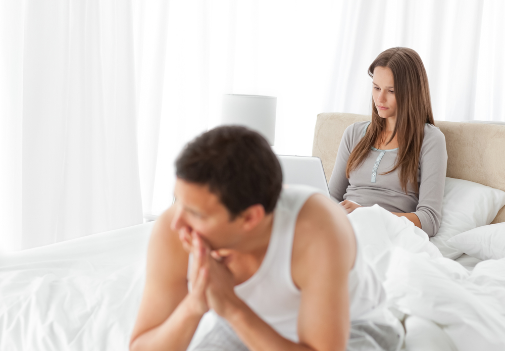Woman working on the laptop while her boyfriend is worrying